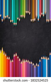 Wave border of colorful wooden pencils on a blank blackboard, back to school concept, vertical.