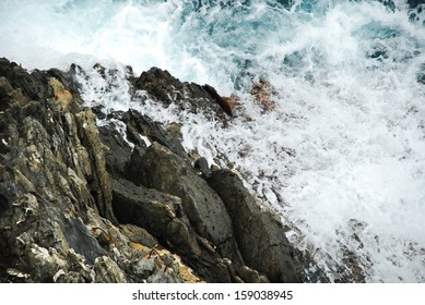 Wave breaking against cliff in Cinque Terre, Italy, view from above