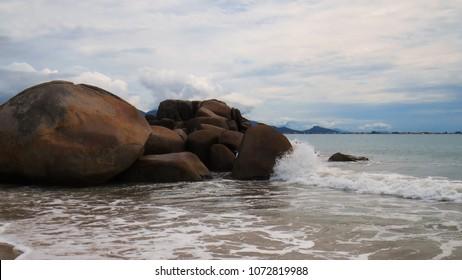 wave breaking on the rocks of the beach De Cima generating a lot of foam, under a cloudy sky, Pinheira, SC, Brazil