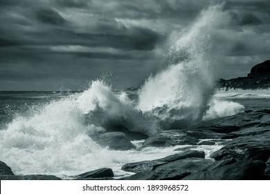 Wave breaking on rocky shore under cloudy sky