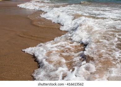 A wave breaking onto the sandy beach on Hawaii