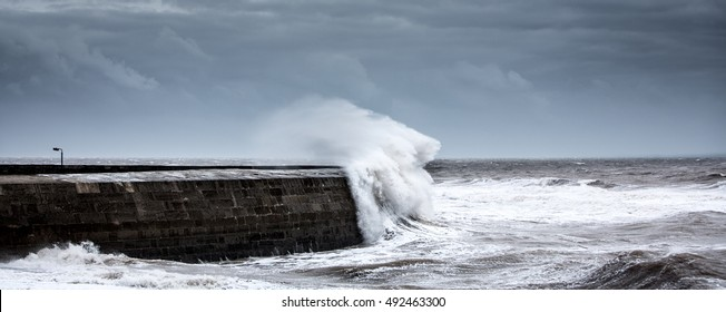 A wave breaking over the Cobb at Lyme Regis in England