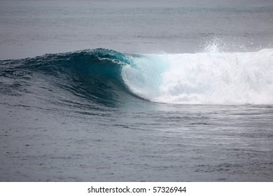 A wave breaks on a shallow coral reef in the Mentawai Island in Indonesia