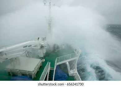 A wave breaks over the bow of a ship during rough seas on the Drake Passage between South Georgia Island and the Antarctic Peninsula