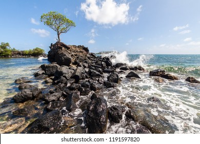 Wave breaks over prehistoric ruined wave breaker made of basalt slabs to shallow lagoon of corals and sand on outskirts of ancient Nan Madol ruined town in Pohnpei, Micronesia, Oceania