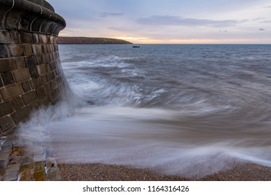 Wave breaks over the slipway and hits the sea wall, incoming morning tide at Filey, North Yorkshire, UK.