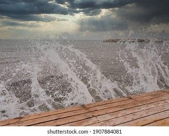 A wave breaks over a wooden platform in the shore area of the Aegean Sea in windy weather