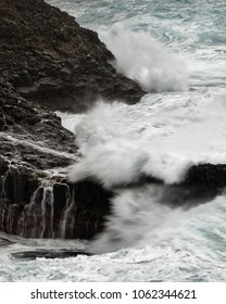 A wave breaks in stormy weather on a reef in front of a rocky coast, water movement in long exposure - Location: Spain, Canary Islands, La Palma