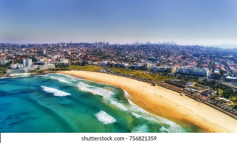 Wave breaks and surf on clear sand of famous Australian Sydney Bondi beach in aerial view with city CBD in background.