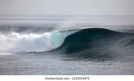 A wave breaks unridden on a shallow coral reef in the Mentawai Islands - Indonesia