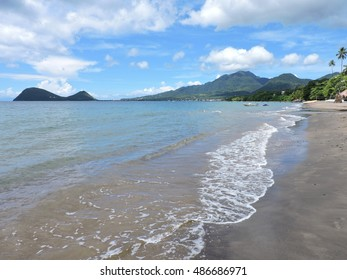 Wave coming on the sand beach, which is leading to mountain view. Dominica, Caribbean