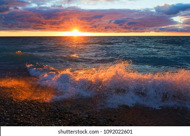 A wave crashes and is highlighted by the setting sun on Lake Michigan at Sleeping Bear Dunes