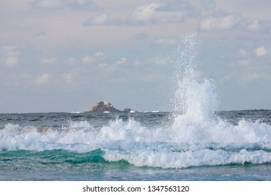 Wave crashes onto the wreck at Byron Bay with Julien Rocks in the background.