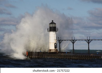 a wave crashing against the Lake Michigan Light House on a cold winter day in St. Joesph, Michigan