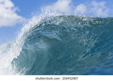 Wave Crest/ a wave peaks and crests against a blue sky