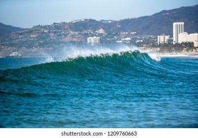 A wave crests and the wind sprays the ocean into the air as wave breaks near beach along Pacific coastline.