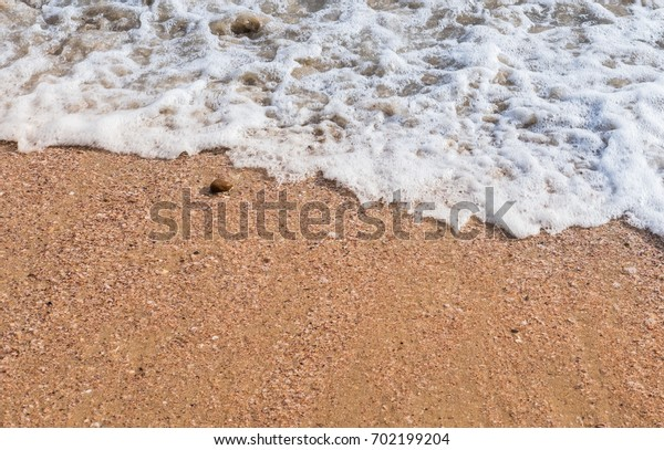 Wave is flowing on sand at beach.