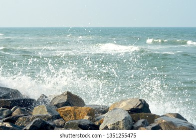 A wave has broken over some rocks, spraying white foam into the air. Waves on the ocean spread to the horizon. The sky is blue.
