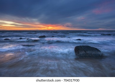 Wave hitting the stones on sand beach at coast of sea water in autumn evening sunset sky clouds light