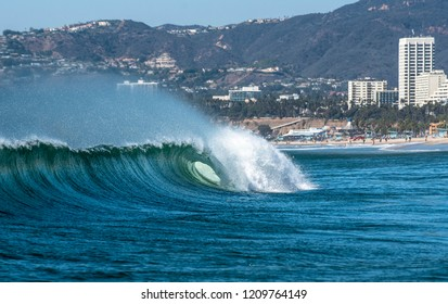 A wave with perfect shape breaks in the ocean along a city beach.