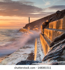 A wave rushes towards the viewer along the pier wall at sunset in Aberystwyth, West Wales, UK.  The side of the wall is lit by the setting sun, a long exposure softens the wave.