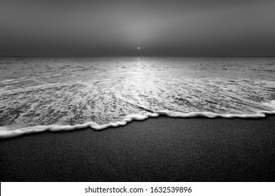 Wave and sandy beach in black and white. Calm view during sunset at seaside.