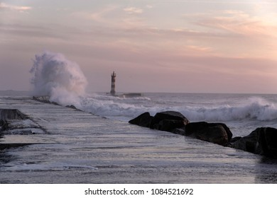 Wave splash at sunset or dusk. Ave river pier and beacon mouth, north of Portugal.