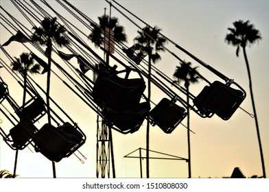 Wave Swinger and Riders at Carnival Fair Silhouette Sunset