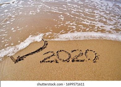 the wave washes away the heart drawn in the sand and the inscription 2020
