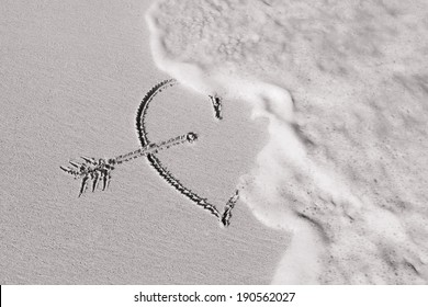 Wave washes over heart in the sand. Love and heart break concept.