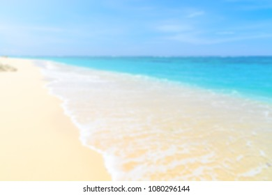 Wave washing over the sand on a tropical white sand beach - blurred background image