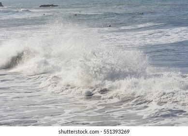 Wave which bursts, beach in Tahiti with surfers