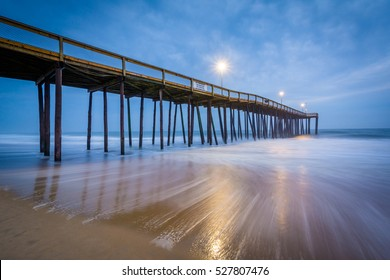 Waves in the Atlantic Ocean and the fishing pier at twilight, in Ocean City, Maryland.