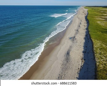 Waves from the Atlantic Ocean wash against a scenic beach on Cape Cod, Massachusetts. This sandy peninsula is a popular summer vacation destination and is also known for its many Great White sharks.