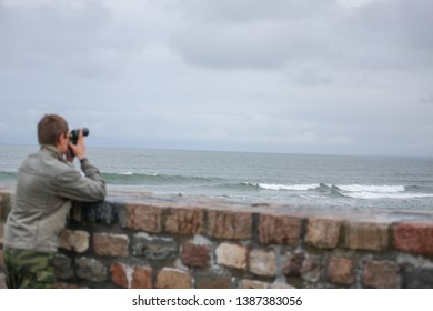 The waves of Baltic sea and the photografer on the shore on the grey sky with clouds background. Baltic sea background