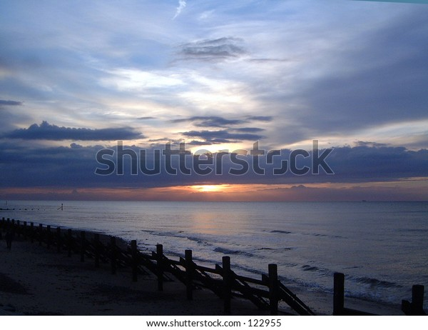 waves beach shore sea sun shadow light golden sunset clouds grass flowers cliff top