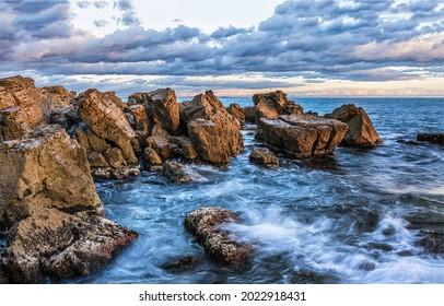 Waves beat against the coastal sea rocks. Coastal sea rocks. Sea rocks view