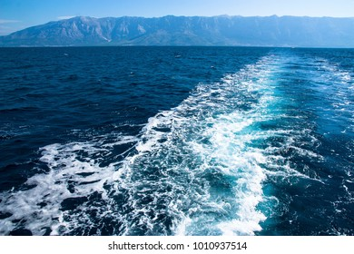 Waves behind a boat with mountains in the background. Croatia, Europe