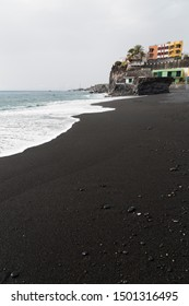 Waves at the black beach of Puerto Naos in La Palma, Spain with the village in the background.