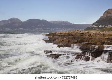 waves braking on a rocky coastline in the background coastal villages