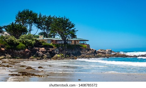 Waves break on the beach at Carmel by the Sea, along the central Coast of California, with luxury houses on the adjacent hillside bluffs.