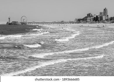 The waves breaking in front of Scheveningen in black and white. In the background the famous Scheveningen skyline, boulevard and pier.