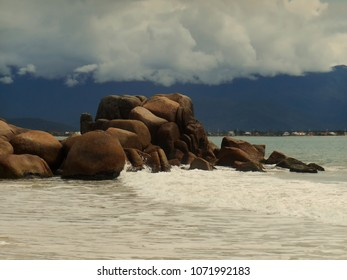 waves breaking gently in rocks of curious shapes at the tip of the beach De Cima, pinheira, SC, brazil