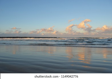 Waves are breaking on a beach. The sky is blue, with the clouds catching the colours of sunset, which are then reflected in the water. A rocky headland is in the distance.