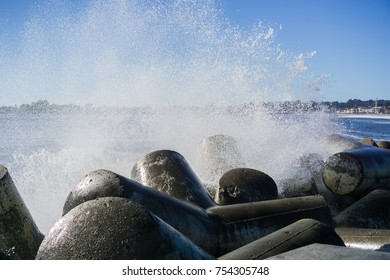 Waves breaking on the concrete blocks protecting the jetty of Santa Cruz Harbor, California