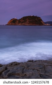 The waves breaking on the rocks at nightfall, with Getaria in the background, Basque Country