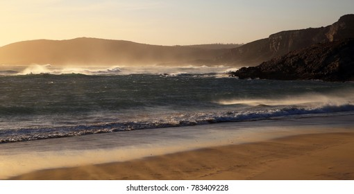 Waves breaking on a rocky shore at sunset, Robberg, Plettenberg bay, South Africa