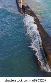 waves breaking on sea wall