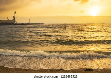 Waves breaking on the shore of Compostela beach in Vilagarcia de Arousa at golden sunset