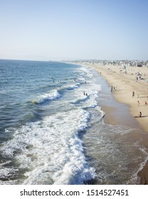 Waves breaking on the shore of Hermosa Beach, California in the middle of the day as people swim in the water.
